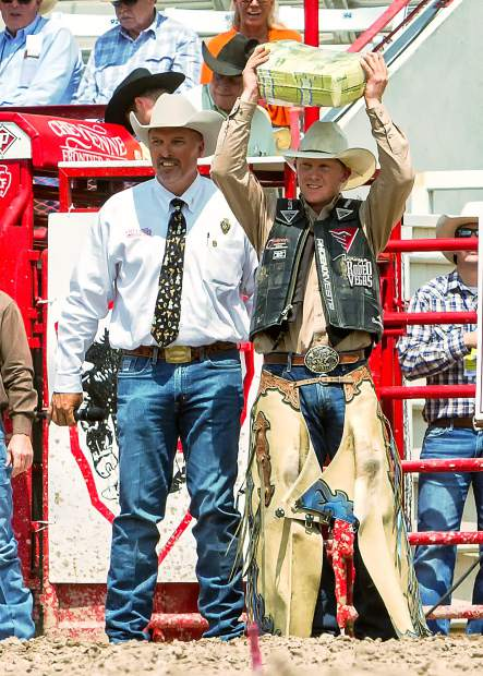 Saddle Bronc rider Taos Muncy happily lifts aloft his $10,000 money bundle for winning his event at the Cinch Shootout. CFD General Chairman, Darin Westby (left) made the cash presentation to the winners.