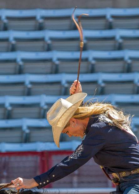 Lainie Whitmire of Colorado urges the last bit of speed from her horse as he runs for the timing line at Cheyenne Frontier Days.