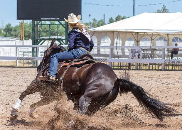 Lainie Whitmire of Colorado stays centered on her horse as he completes the turn on barrel No. 1 and starts looking for barrel No. 2, during Cheyenne Frontier Days.