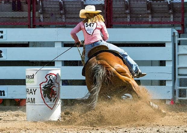 Kelly Kennedy - Joseph of Berthoud, Colorado and her horse dive into the barrel #2 turn during Cheyenne Frontier Days Barrel Racing Slack. Kennedy - Joseph finishes with an 18.01second run.