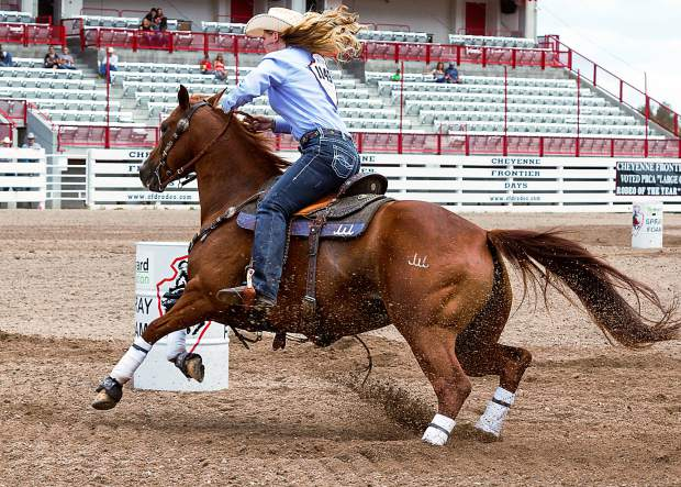 Lainie Whitmire from Marietta, Oklahoma makes a clean turn at the beginning of her run as she takes aim on barrel #2 at the 120th Cheyenne Frontier Days.