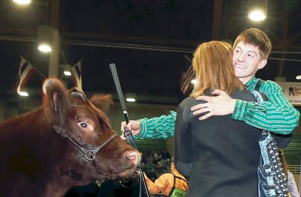 Shilo Schaake, right, of Westmoreland, Kan., hugs his mother Kandi, after the boy's 1,369-pound steer named Red Rocky was selected as the grand champion market beef at the 109th annual National Western Stock Show and Rodeo Thursday, Jan. 22, 2015, in Denver. Stockgrowers from across the country and Canada are taking part in the National Western, which is one of the largest livestock exhibiitons staged in North America. (AP Photo/David Zalubowski)
