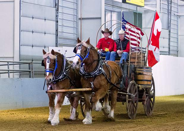 Owner and driver of the authentic Birdsell Chuckwagon, Leroy Leavitt of Severance, Colorado, presents the USA and Canadian colors at the 12th annual Big Thunder Draft Horse Show held at The Ranch in Loveland, Colorado. His team is a pair nineteen year old Belgian half-brothers.