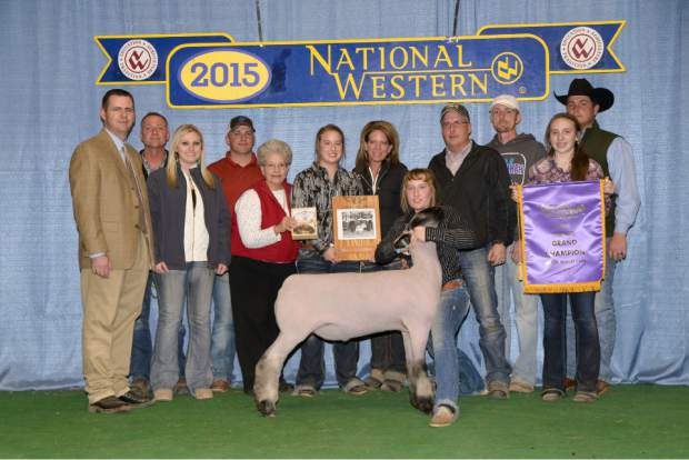 Jenna Frink shows off her Grand Champion blackface lamb Unfinished Business at the National Western Stock Show. Standing with her are lamb show Judge Josh Cody, Mark Overman, Landree MacLennan, Lance MacLennan, Mavis Davis, Kayla Frink, Amy Frink, Jenna Frink, Mike Frink, Chad Walker, Lauren Frink and Shane Bedwell.