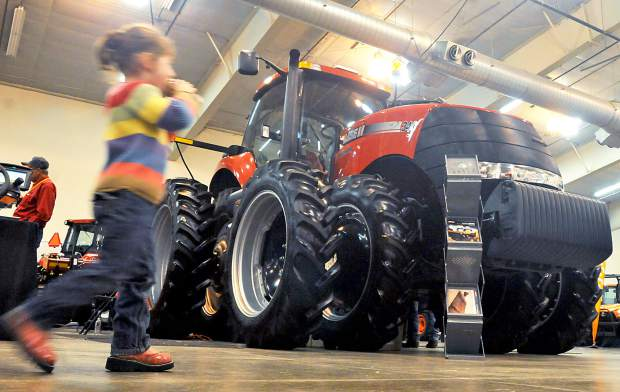 People pass by some of the tractors on display at the Colorado Farm Show on Thursday in the Island Grove Events Center in Greeley.