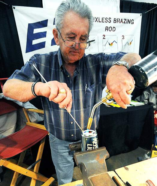 Don Wilke uses a EZ Fluxless Brazing Road to show the strength of the product after puncturing and then sealing a beer can on Tuesday at the Colorado Farm Show in Greeley. The Tuesday-Thursday farm show included numerous exhibition booths and farm equipment to see.