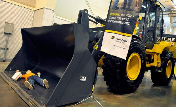 The bucket of a tractor gives Connor Rosling a nice spot to take a break after exploring the Colorado Farm Show Thursday morning at the Island Grove Events Center in Greeley.