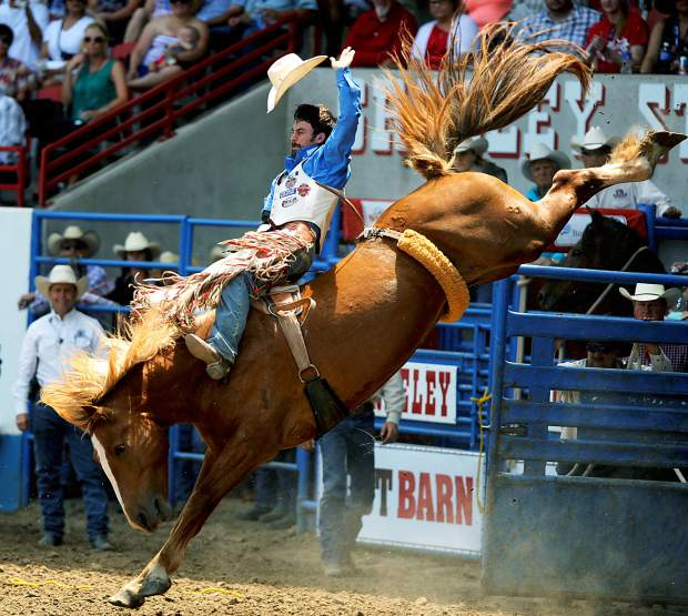 Win Ratliff holds on to Red Bandana during the bareback riding finals at the Greeley Stampede Rodeo in the Stampede Arena on Saturday.