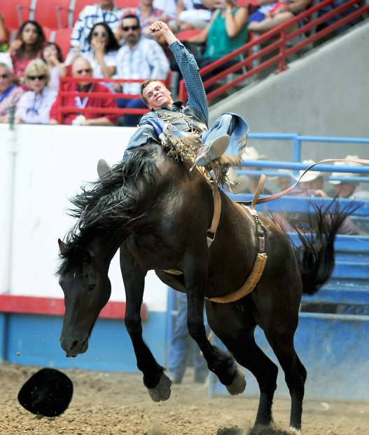 Orin larsen struggles to keep hold of Black Kat during the bareback bronc riding finals at the Greeley Stampede in the Stampede Arena.