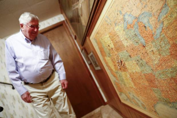 Bill Webster looks at a map in his basement where he placed pins to the cities he has traveled.