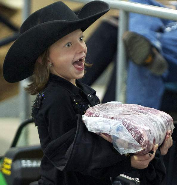 Oliva Betsworth, 7, holds a large ribeye for sale during the 18th annual Boys & Girls Clubs of Weld County Calf Auction on Saturday at the Producers Livestock Marketing Association, 711 O St. in Greeley.