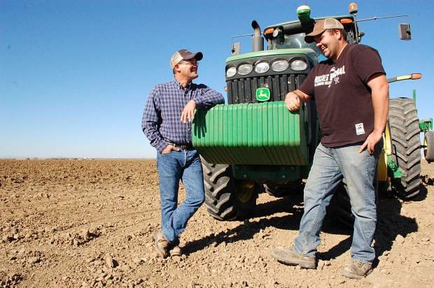 Marc Arnusch talks with one of his employees, Casey Cantwell, at his farm in Keenesburg. Cantwell said Arnusch has been a great employer and has done a good job keeping up with the latest technologies on the farm, which is Cantwell's area of specialty.