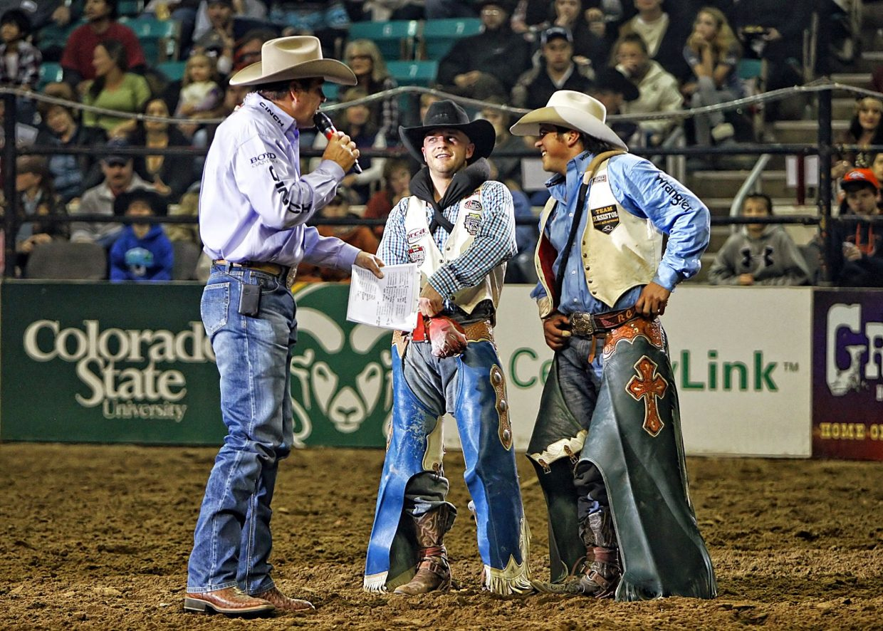 Rodeo announcer Boyd Polhamus interviewed Seth Hardwick (center) and Richie Champion (right) on the arena floor after their high point rides in the final round qualified them to ride against each other in a winner take all head-to-head round for a further $10,000. The cowboys had the chance to choose the bronc they wanted to ride and explain their choice to the crowd. Champion was the eventual winner after a record breaking 92-point ride later in the evening.