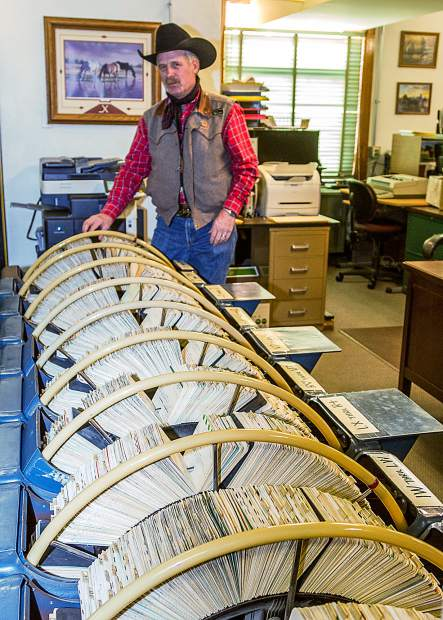"""Rick Wahlert, the Technical Coordinator in the Brand Inspectors office, gives a sense of scale to the roughly twelve foot long """"rolodex"""" filing system containing the 35,000 cards representing the current brands in the state of Colorado."""