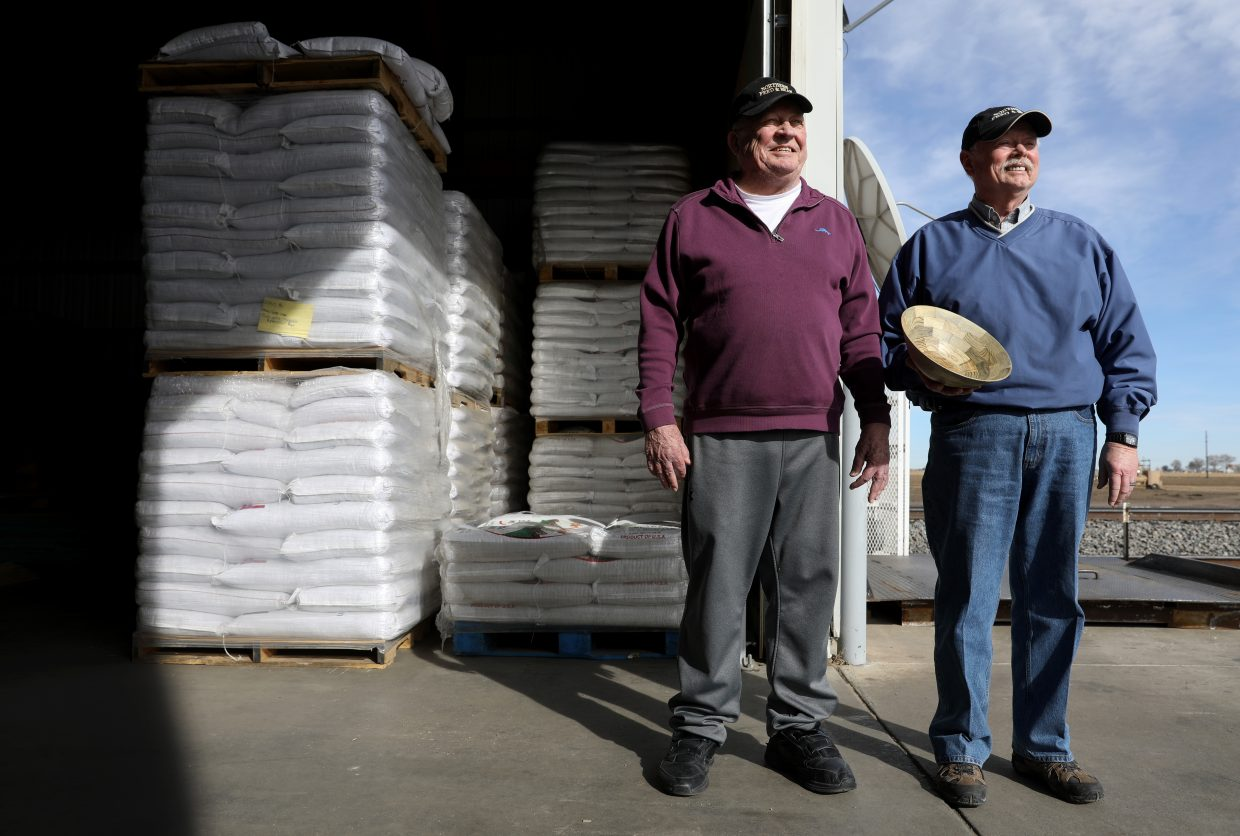 Former owner and current consultant Bob Brunner, left, and owner and general manager Larry Lande of Northern Feed and Bean stand in their warehouse holding their award Wednesday located at 33278 U.S. 85 in Lucerne. The company was recognized with the Experience Export Award at the Governors Form on Colorado Agriculture on Feb. 22 of this year.