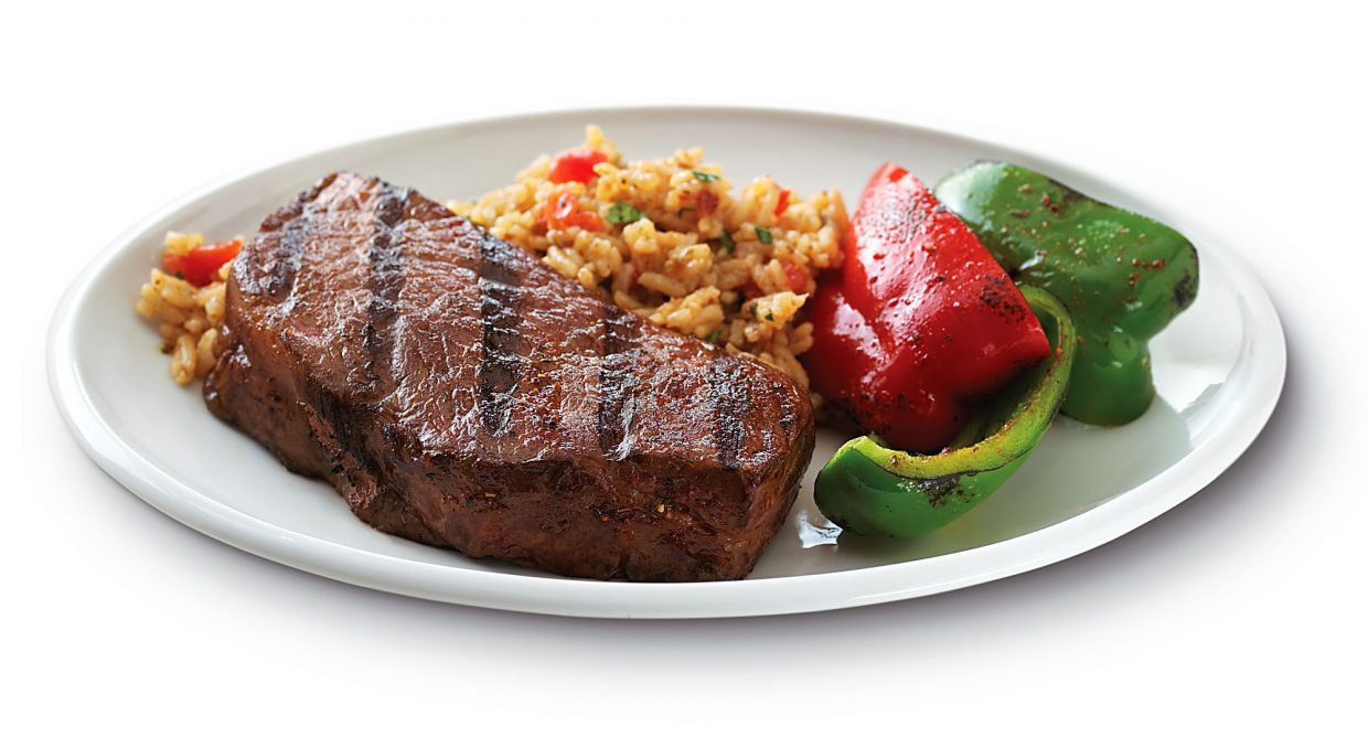 A dinner plate holds a grilled Denver Steak, with peppers and rice.