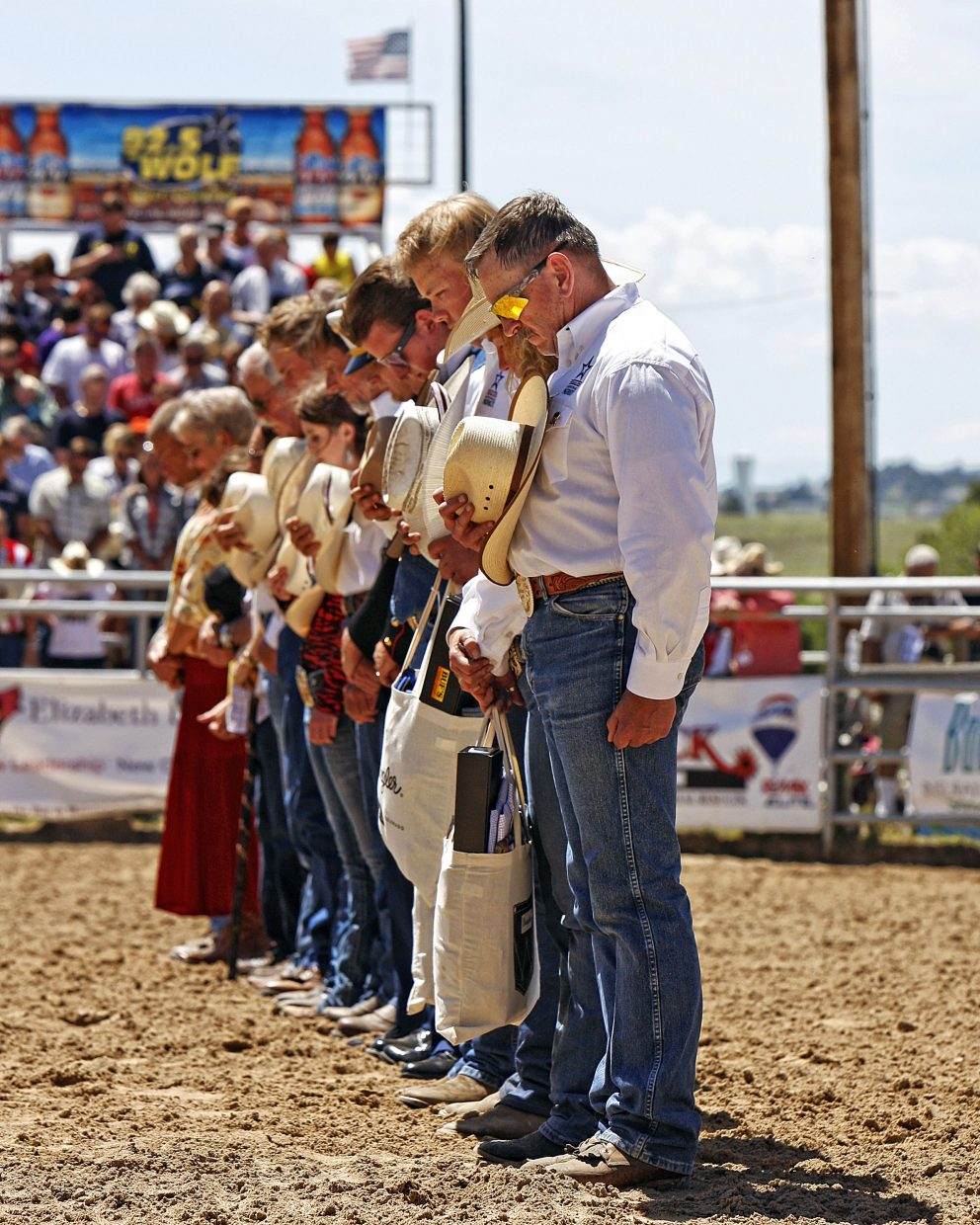 The Elizabeth Stampede's Red, White & Blue Rodeo Coordinator, Frank Harman (right), bows his head in prayer along with the veterans being honored inside the arena before the start of the performance that honored the military on June 4.