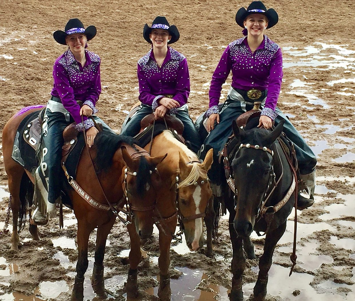 At the 2017 Pikes Peak or Bust Rodeo's Saturday night performance, three Rangerettes pose during the Grand Entry. A little rain didn't dampen the spirits of (left to right) Ashleigh Barnes riding Luna, Sydney Nelson on Rango, and Natalie Smith atop Tasia.