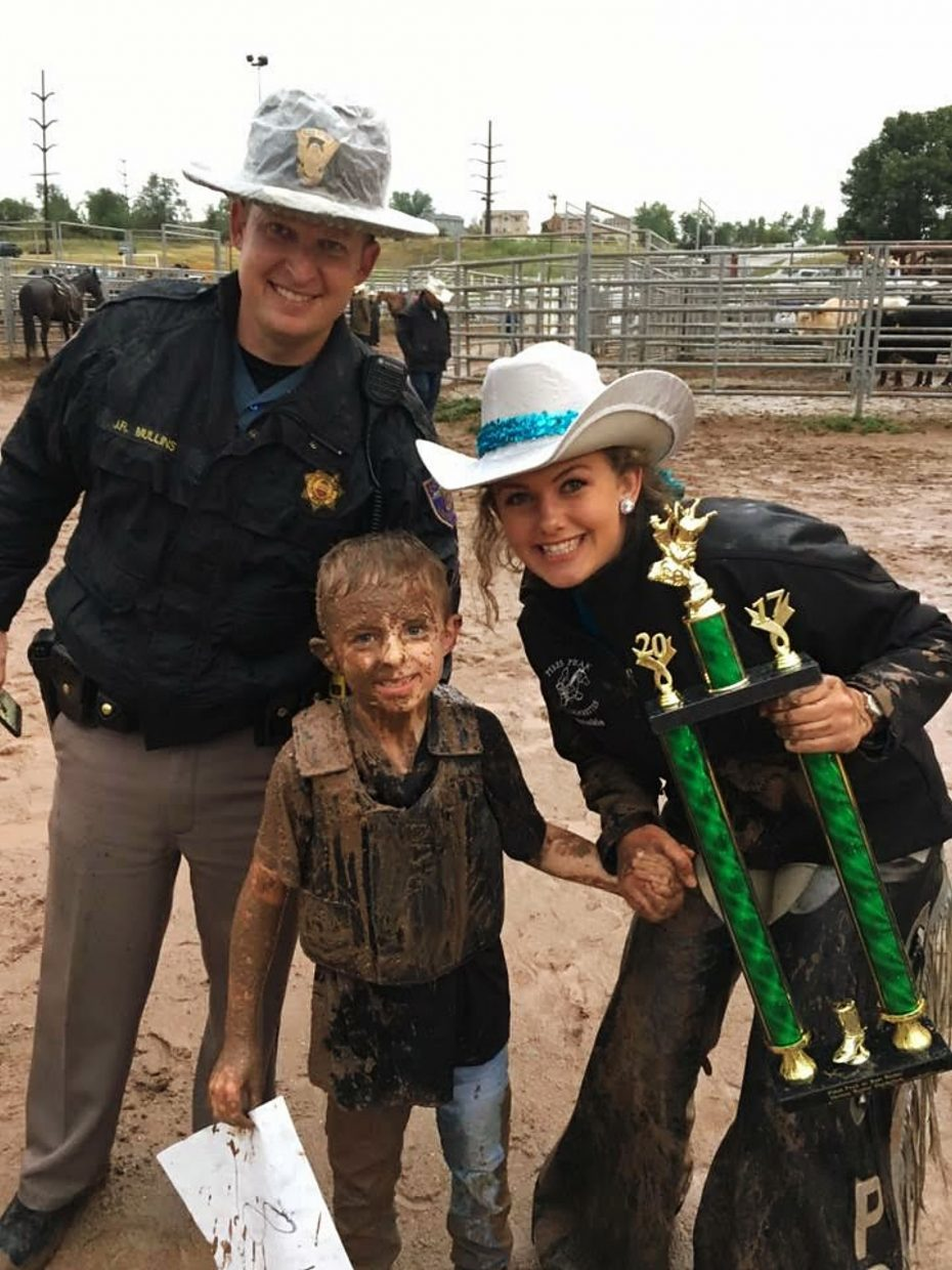 Frankie Henderson, winner of the mutton busting event, accepts his enormous trophy from a Rangerette and an event volunteer Colorado Springs Police Officer. A little mud. just made the 2017 Pikes Peak or Bust Rodeo all the better for Frankie.