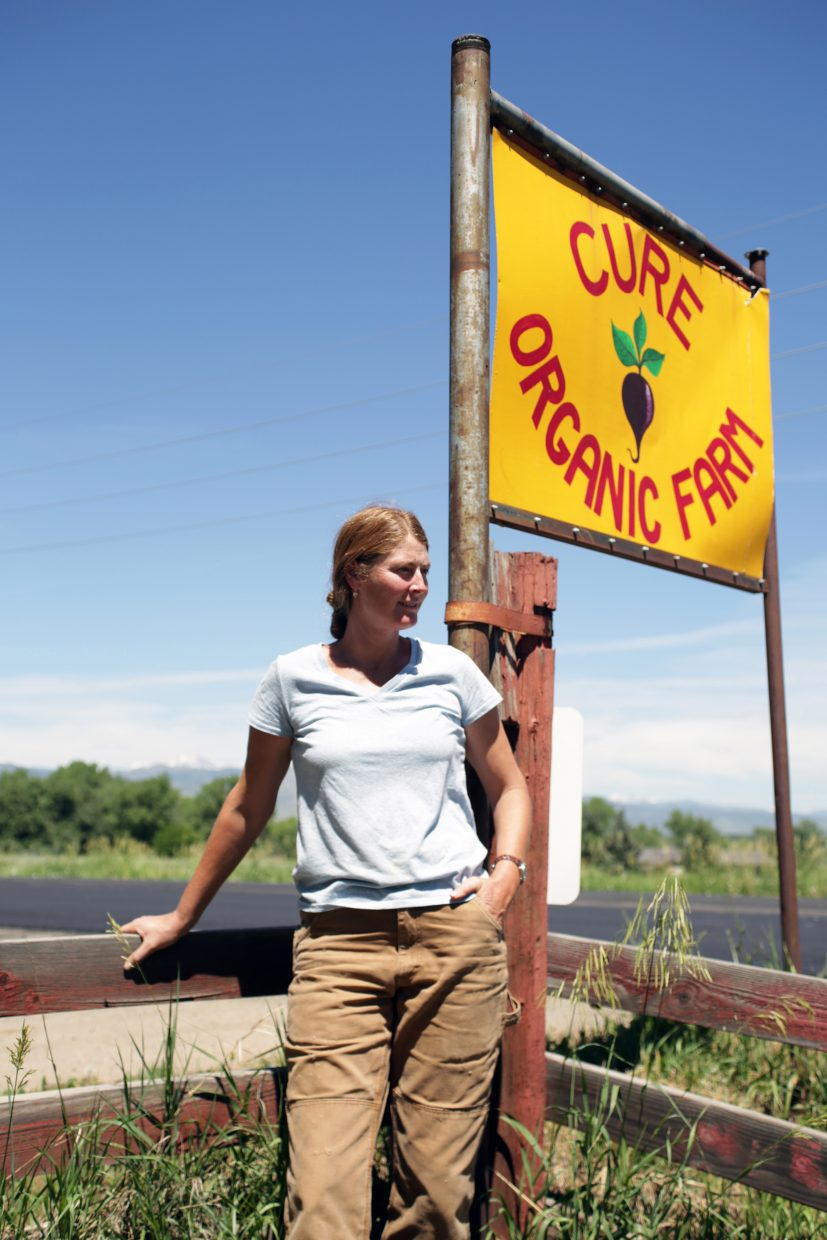 Anne Cure, co-owner of the Cure Organic Farm, stands in front of her farm's sign on Thursday in Boulder at 7416 Valmont Road. Cure and her husband Paul Cure opened up the farm in 2005 and have many passionate interns and volunteers working in the farm to keep it up and running.