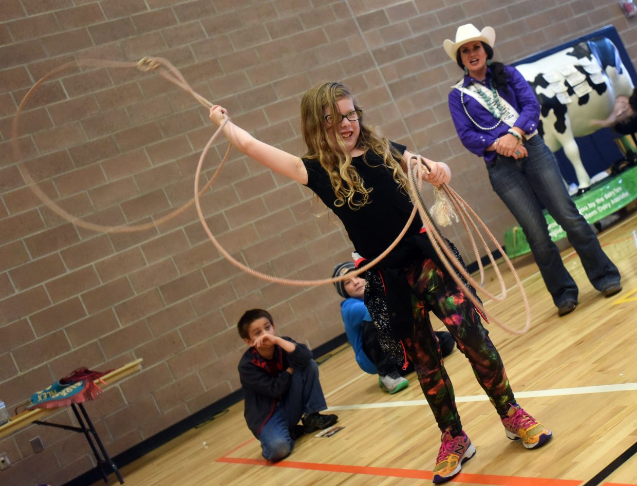 Tess Cooper, 9, tries out roping as Alex Hyland watches during the agriculture education fair on Sept. 25 at the Windsor Recreation Center in Windsor, Colo.