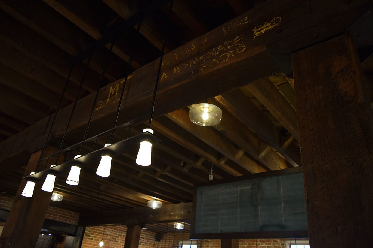 The walls and decor stay true too the building's 110-year-old history. This picture of the cafe ceiling shows writing kept on the original wood in the historic mill, along with the chalk board in the background the mill previously used for orders.