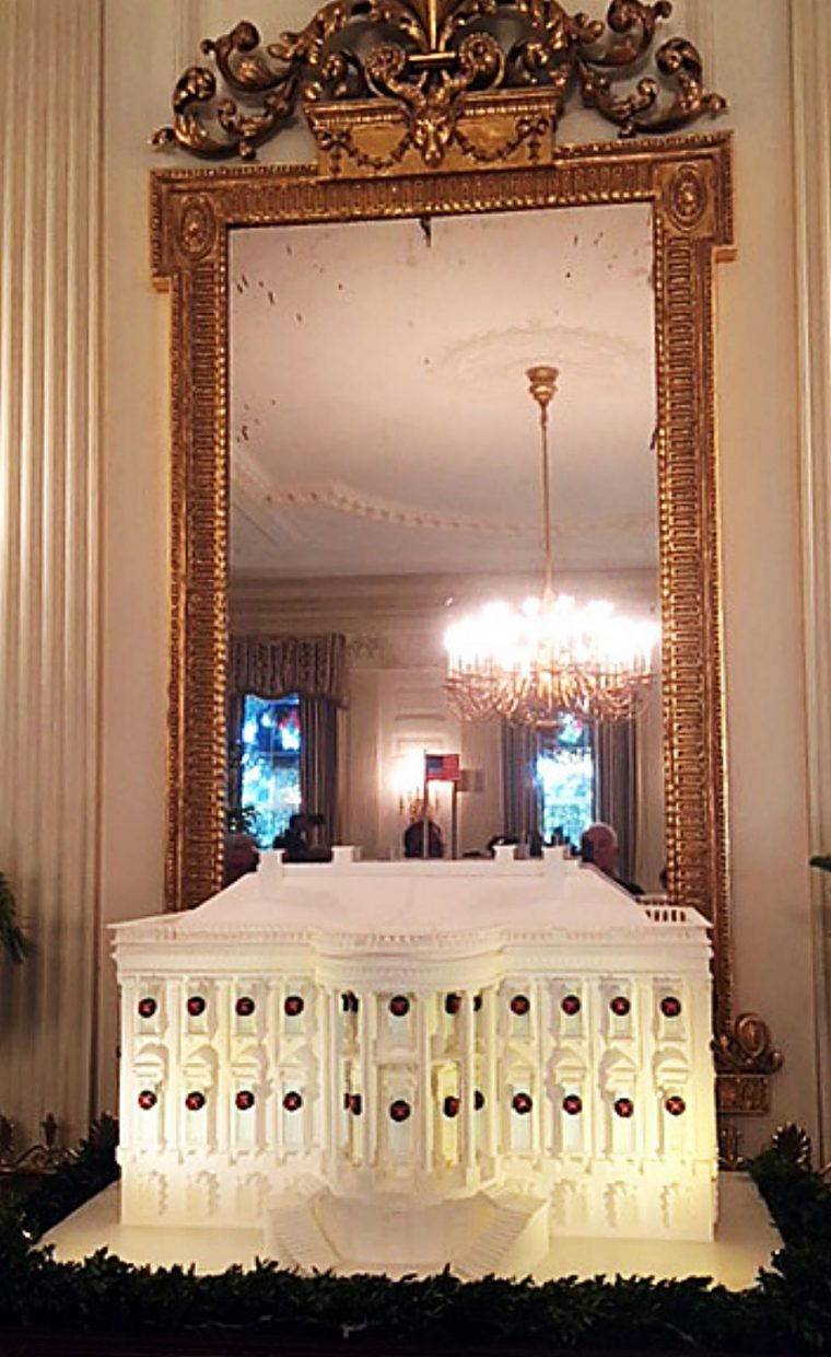 The gingerbread White House is decorated with miniature Christmas wreaths, reflecting the first lady's preference for classic Christmas decor.