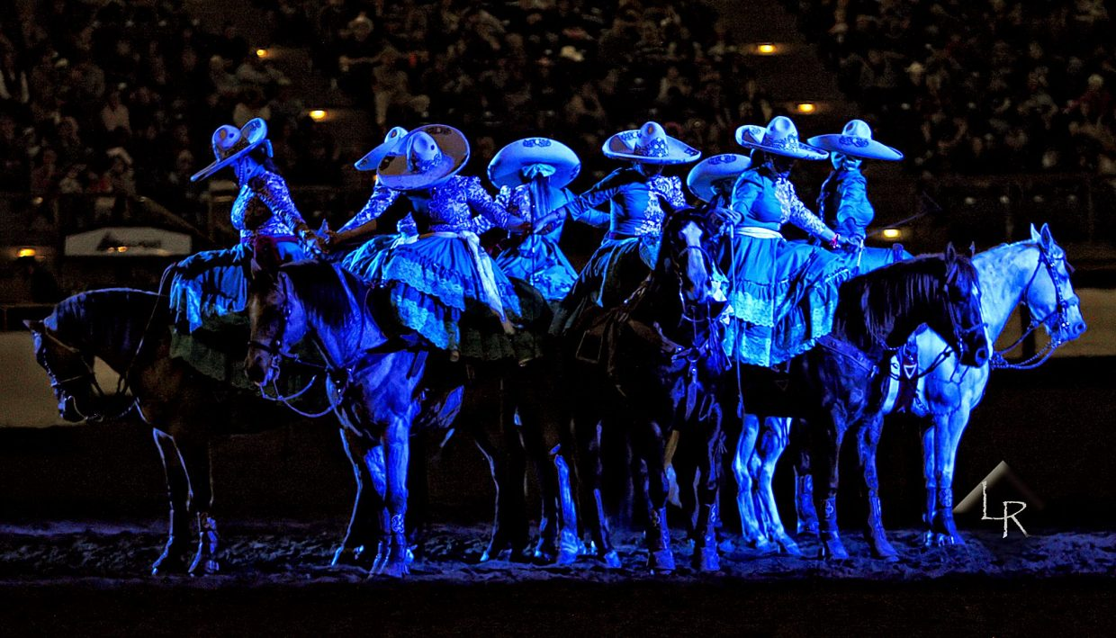 The Escaramuzas, who ride side saddle, participate in their traditional ending prayer under soft blue lights in the Wild West Show at the 2019 National Western Stock Show.